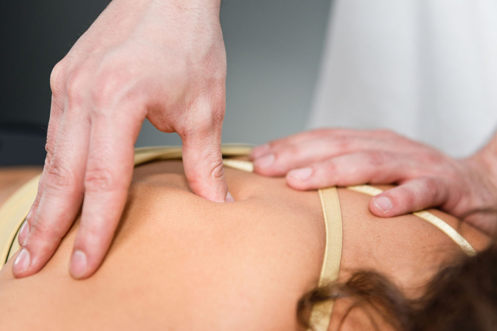 Chiropractor giving deep tissue massage to patient